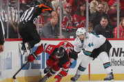 Referee Greg Kimmerly #18 jumps out of the way as Marc-Edouard Vlasic #44 of the San Jose Sharks holds up Kyle Palmieri #21 of the New Jersey Devils during the first period at the Prudential Center on October 14, 2018 in Newark, New Jersey.