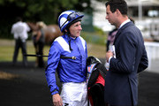 Paul Hanagan (L) chats with Charlie Hills at Sandown racecourse on August 31, 2012 in Esher, England.