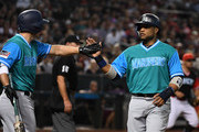 Robinson Cano #22 of the Seattle Mariners celebrates with Kyle Seager #15 after scoring on a double by teammate Denard Span #4 during the third inning against the Arizona Diamondbacks at Chase Field on August 24, 2018 in Phoenix, Arizona. The players are wearing special jerseys as part of MLB Players Weekend.