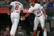 Justin Upton #8 of the Los Angeles Angels of Anaheim is congratulated by Jose Fernandez #20 of the Los Angeles Angels of Anaheim after hitting a home run against the Seattle Mariners in the fourth inning at Angel Stadium on September 15, 2018 in Anaheim, California.