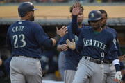 Nelson Cruz #23 of the Seattle Mariners is congratulated by Dee Gordon #9 after Cruz scored against the Oakland Athletics in the top of the first inning at Oakland Alameda Coliseum on August 30, 2018 in Oakland, California.