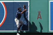 Denard Span #4 of the Seattle Mariners comes down with the ball after making a catch above the center field wall for the out during the seventh inning of the MLB game against the Los Angeles Angels of Anaheim at Angel Stadium on July 29, 2018 in Anaheim, California.