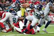 Running back Mike Davis #27 of the Seattle Seahawks scores a one-yard touchdown while being tackled by defensive back Bene' Benwikere #23 of the Arizona Cardinals during the third quarter at State Farm Stadium on September 30, 2018 in Glendale, Arizona.