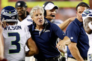 Head coach Pete Caroll of the Seattle Seahawks congratulates quarterback  Russell Wilson #3 after a touchdown during the NFL preseason game against the Kansas City Chiefs at Arrowhead Stadium on August 24, 2012 in Kansas City, Missouri.