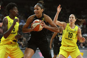 A'ja Wilson #22 of the Las Vegas Aces drives against Natasha Howard #6 and Sue Bird #10 of the Seattle Storm during the Aces' first-ever home game at the Mandalay Bay Events Center on May 27, 2018 in Las Vegas, Nevada. NOTE TO USER: User expressly acknowledges and agrees that, by downloading and or using this photograph, User is consenting to the terms and conditions of the Getty Images License Agreement.