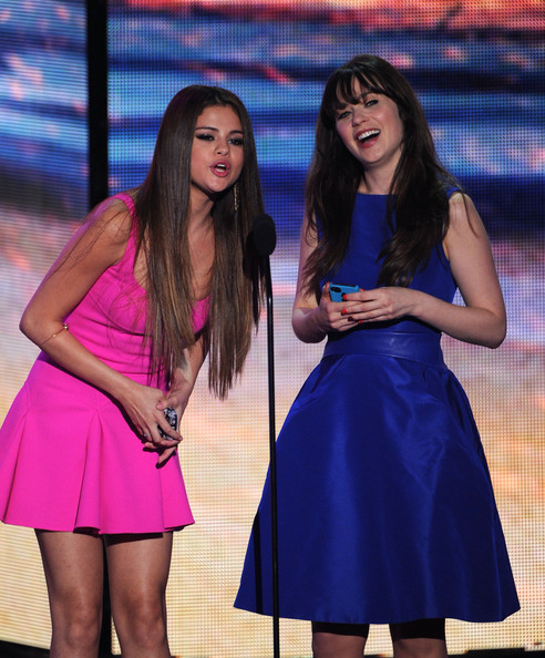 Selena Gomez Actresses Selena Gomez (L) and Zooey Deschanel speak onstage during the 2012 Teen Choice Awards at Gibson Amphitheatre on July 22, 2012 in Universal City, California.