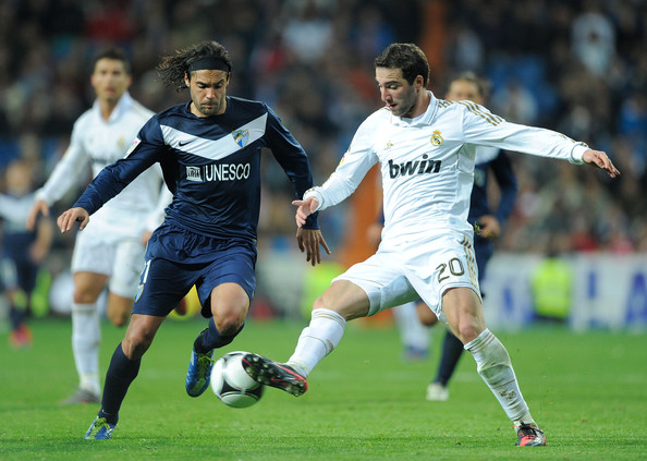 Sergio Sanchez Gonzalo Higuain (R) of Real Madrid controls the ball while being challenged by Sergio Sanchez of Malaga during the round 16 Copa del Rey 1st leg match between Real Madrid and Malaga at Bernabeu on January 3, 2012 in Madrid, Spain.