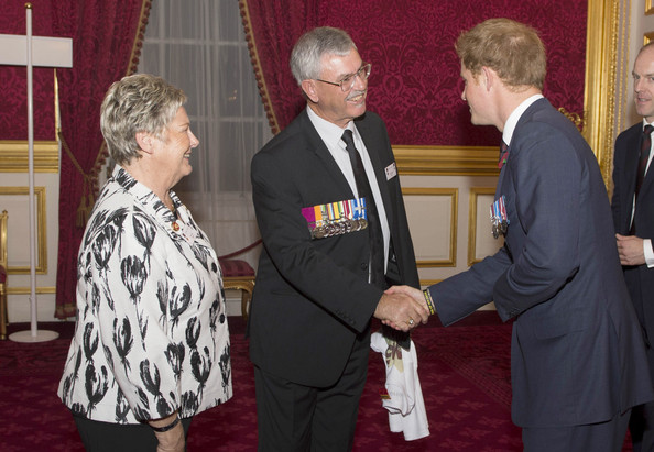 "Mr and Mrs Baird present Prince Harry with a ""Cams Cause"" t-shirt, a charity dedicated to the legacy of Corporal Cameron Baird VC MG, during the President's Party in remembrance and re-dedication for members of the Victoria Cross and George Cross Association in the State Apartments at St James's Palace on October 29, 2014 in London, England."