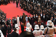 """(R-L) Producer Simon Emanuel, Actor Joonas Suotamo, Chewbacca, actor Woody Harrelson, director Ron Howard, actress Emilia Clarke, actor Alden Ehrenreich, actor Donald Glover, actress Phoebe Waller-Bridge, actor Paul Bettany, producer Kathleen Kennedy, writer Lawrence Kasdan, screenwriter Jonathan Kasdan look up to stormtroopers as they attend the screening of """"Solo: A Star Wars Story"""" during the 71st annual Cannes Film Festival at Palais des Festivals on May 15, 2018 in Cannes, France."""