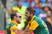 Imran Tahir congratulates Faf du Plessis of South africa after he took a catch to dismiss Virat Kohli of India during the 2015 ICC Cricket World Cup match between South Africa and India at Melbourne Cricket Ground on February 22, 2015 in Melbourne, Australia.