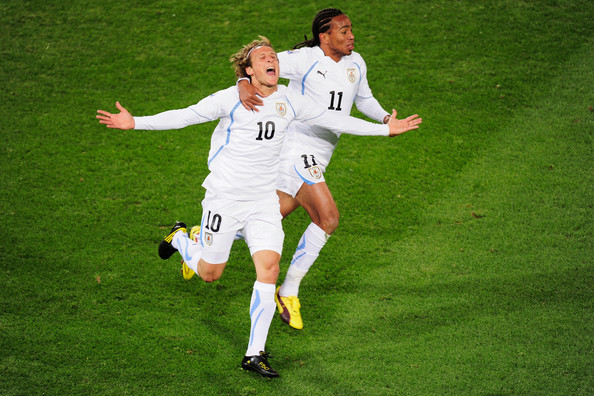 Diego Forlan of Uruguay celebrates after scoring the opening goal with team mate Alvaro Pereira (R) during the 2010 FIFA World Cup South Africa Group A match between South Africa and Uruguay at Loftus Versfeld Stadium on June 16, 2010 in Tshwane/Pretoria, South Africa.