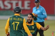Imran Tahir of the Proteas celebrates the wicket of Dwayne Smith of the West Indies with AB de Villiers of the Proteas during the 1st Momentum ODI between South Africa and West Indies at Sahara Stadium Kingsmead on January 16, 2015 in Durban, South Africa.