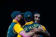 Imran Tahir of South Africa (R) hugs AB de Villiers of South Africa after dismissing Tinashe Panyangara of Zimbabwe during the 2015 ICC Cricket World Cup match between South Africa and Zimbabwe at Seddon Park on February 15, 2015 in Hamilton, New Zealand.