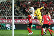 Diego Godin of Uruguay competes for the ball with goalkeeper Kim Seung-Gyu of South Korea during the international friendly match between South Korea and Uruguay at the Seoul World Cup Stadium on October 12, 2018 in Seoul, South Korea.