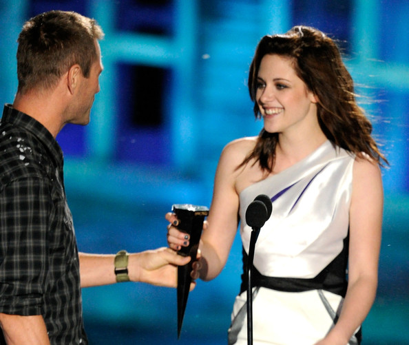 """Actress Kristen Stewart (R) accepts the Best Fantasy Actress award from actor Aaron Eckhart onstage during Spike TV's """"Scream 2010"""" at The Greek Theatre on October 16, 2010 in Los Angeles, California."""