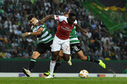 Danny Welbeck of Arsenal FC is brought down by Marcos Acuna and Bruno Gaspar of Sporting Club during the UEFA Europa League Group E match between Sporting CP and Arsenal at Estadio Jose Alvalade on October 25, 2018 in Lisbon, Portugal.