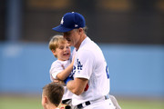 Chase Utley #26 of the Los Angeles Dodgers leads his boys, Max and Ben, off the field after throwing out a ceremonial first pitch before the game against the St. Louis Cardinals at Dodger Stadium on August 22, 2018 in Los Angeles, California.