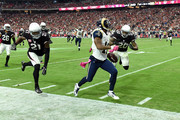 Wide receiver Tavon Austin #11 of the St Louis Rams runs past cornerback Patrick Peterson #21 of the Arizona Cardinals (left) and safety Deone Bucannon #20 (right) during the fourth quarter of the NFL game against the Arizona Cardinals at University of Phoenix Stadium on October 4, 2015 in Glendale, Arizona.