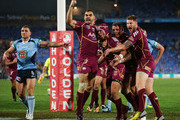 Johnathan Thurston (C) of the Maroons celebrates with Greg Inglis (L) after scoring the first try as Robbie Farah (L) protests during game three of the ARL State of Origin series between the New South Wales Blues and the Queensland Maroons at ANZ Stadium on July 17, 2013 in Sydney, Australia.