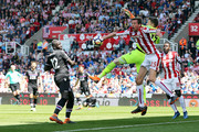 Wayne Hennessey of Crystal Palace and Peter Crouch of Stoke City battle for the ball as Mamadou Sakho of Crystal Palace looks on during the Premier League match between Stoke City and Crystal Palace at Bet365 Stadium on May 5, 2018 in Stoke on Trent, England.