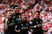 Philippe Coutino of Liverpool celebrates after scoring the winning goal with team mates Emre Can,Roberto Firmino and James Milner during the Barclays Premier League match between Stoke City and Liverpool at Britannia Stadium on August 9, 2015 in Stoke on Trent, England.