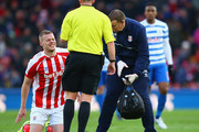 Referee Mike Dean looks on as Ryan Shawcross of Stoke City receives treatment during the Barclays Premier League match between Stoke City and Queens Park Rangers at Britannia Stadium on January 31, 2015 in Stoke on Trent, England.