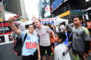 American soccer player Dax McCarty poses with fans during the Street Soccer USA Cup at Times Square on July 9, 2016 in New York City.
