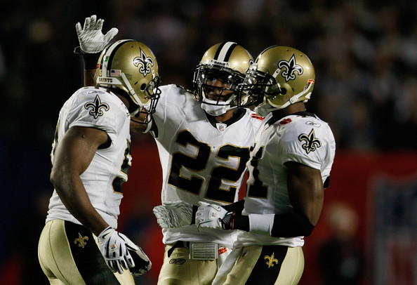 Jonathan Vilma #51, Tracy Porter #22 and Roman Harper #41 of the New Orleans Saints celebrate after a play against the Indianapolis Colts during Super Bowl XLIV on February 7, 2010 at Sun Life Stadium in Miami Gardens, Florida.