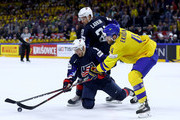 Mattias Ekhol #4 of Sweden and Cam Atkinson of the United States battle for the puck during the 2018 IIHF Ice Hockey World Championship Semi Final game between Sweden and USA at Royal Arena on May 19, 2018 in Copenhagen, Denmark.