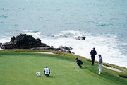 Patrick Reed of the United States lines up a putt as Phil Mickelson of the United States and Scott Ozanus, Deputy Chairman and Chief Operating Officer of KPMG, look on during the third round of the AT&T Pebble Beach Pro-Am at Pebble Beach Golf Links on February 09, 2019 in Pebble Beach, California.