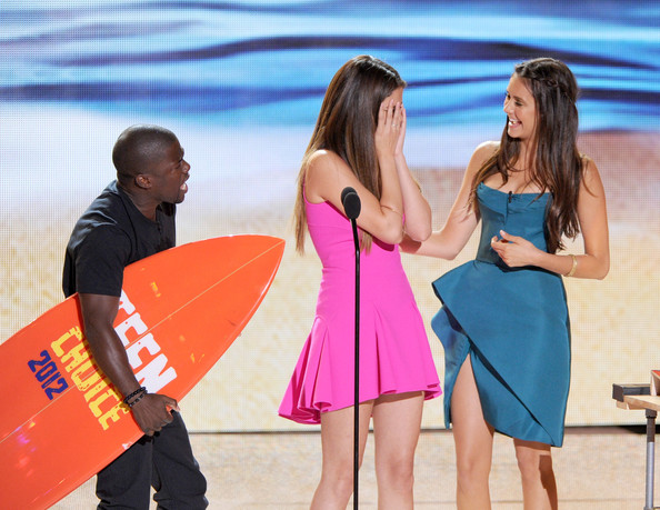 Singer Selena Gomez (C) accepts the Choice Music Group award from actors Kevin Hart and Nina Dobrev onstage during the 2012 Teen Choice Awards at Gibson Amphitheatre on July 22, 2012 in Universal City, California.