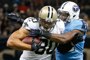 Jimmy Graham #80 of the New Orleans Saints is tackled by Wesley Woodyard #59 of the Tennessee Titans during the first preseason game at Mercedes-Benz Superdome on August 15, 2014 in New Orleans, Louisiana.