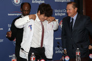 Ron Washington (L) assists Shin-Soo Choo #17 with his new jersey as Choo's agent Scott Boras looks on (R) during the press conference introducing Choo at Rangers Ballpark in Arlington on December 27, 2013 in Arlington, Texas.