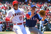 Pitcher Doug Fister #38 of the Texas Rangers and Shohei Ohtani #17 of the Los Angeles Angels of Anaheim the;; Ronald Guzman #67 of the Texas Rangers to hold the throw as Ohtani is safe at first with a single in the second inning of the game aat Angel Stadium on June 3, 2018 in Anaheim, California.