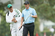 Justin Rose of England with Mark Fulcher after he hits his second shot on the first hole during the first round of the 2013 Masters Tournament at Augusta National Golf Club on April 11, 2013 in Augusta, Georgia.