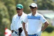 Justin Rose of England waits in the first fairway alongside his caddie  Mark Fulcher during the third round of the 2014 Masters Tournament at Augusta National Golf Club on April 12, 2014 in Augusta, Georgia.