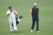 Justin Rose of England walks with caddie Mark Fulcher on the second fairway during the third round of the 2018 Masters Tournament at Augusta National Golf Club on April 7, 2018 in Augusta, Georgia.