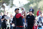 Tiger Woods plays his second shot on the sixth hole as Phil Mickelson looks on during The Match: Tiger vs Phil at Shadow Creek Golf Course on November 23, 2018 in Las Vegas, Nevada.