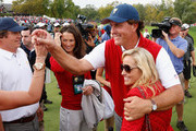 Phil Mickelson of the U.S. Team celebrates with his wife, Amy, and other team members on the 18th hole during the Day Four Singles Matches at the Muirfield Village Golf Club on October 6, 2013  in Dublin, Ohio.