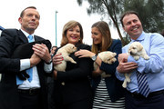 Australian Opposition Leader, Tony Abbott, his daughter Frances, and Liberal MP Josh Frydenberg, hold a puppy at Victoria Guide Dogs on September 6, 2013 in Melbourne, Australia. With just one day left in the campaign the Liberal-National Party coalition had one of their first stumbles, by releasing a policy to implement an opt-out internet filter, but then abandoning it within hours. The conservative Liberal-National Party coalition looks set to form government in tomorrow's Federal Election.