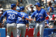 Josh Donaldson #20 and Russell Martin #55 of the Toronto Blue Jays are congratulated by Troy Tulowitzki #2 after the two scored on a single by Kendrys Morales #8 during the third inning of a game against the New York Yankees at Yankee Stadium on July 4, 2017 in the Bronx borough of New York City.
