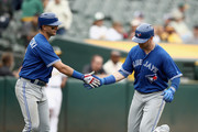 Justin Smoak #14 of the Toronto Blue Jays is congratulated by Troy Tulowitzki #2 after he hit a home run in the 10th inning against the Oakland Athletics at Oakland Alameda Coliseum on June 7, 2017 in Oakland, California.
