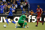 Marco Di Vaio #9 of Montreal Impact moves the ball past Joe Bendik #12 of Toronto FC to score during the MLS game at the Olympic Stadium on March 16, 2013 in Montreal, Quebec, Canada.