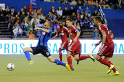 Marco Di Vaio #9 of Montreal Impact moves the ball past Danny Califf #3 and Kyle Bekker #8 of Toronto FC during the MLS game at the Olympic Stadium on March 16, 2013 in Montreal, Quebec, Canada.