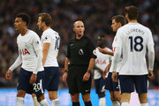 Referee Mike Dean speaks to the Tottenham Hotspur players during the Premier League match between Tottenham Hotspur and Swansea City at Wembley Stadium on September 16, 2017 in London, England.