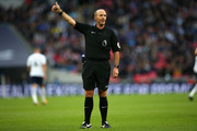 Referee Mike Dean gestures during the Premier League match between Tottenham Hotspur and Swansea City at Wembley Stadium on September 16, 2017 in London, England.
