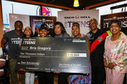 Detroit Lions running back Reggie Bush (L) and $10,000 scholarship winner Bria Gregory (LC) pose with family members at the Touchdown For Teens Campaign at Taco Bell on August 26, 2014 in Royal Oak, Michigan.