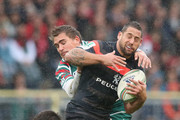 Luke McAlister of Toulouse is tackled by Ben Youngs (L) and Toby Flood during the Heineken Cup match between Toulouse and Leicester Tigers at Le Stadium on October 14, 2012 in Toulouse, France.