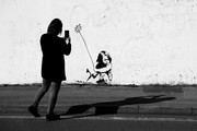 Image has been converted to black and white.) A member of the public takes a photograph on her phone of a Banksy mural that has been modified to depict the current COVID-19  pandemic on April 21, 2020 in Southampton, England. The British government has extended the lockdown restrictions first introduced on March 23 that are meant to slow the spread of COVID-19.