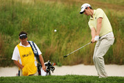 Justin Rose of England plays a shot on the sixth hole as his caddie Mark Fulcher looks on during the continuation of the second round of the 109th U.S. Open on the Black Course at Bethpage State Park on June 20, 2009 in Farmingdale, New York.